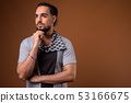 Young bearded Indian man against brown background 53166675