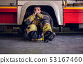 Image of tired fireman sitting on floor near red fire truck 53167460
