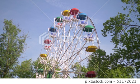 A colorful ferris wheel on a background of blue sky and green trees 53172023