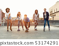 Group of smiling teenagers with roller skates and skateboard 53174291