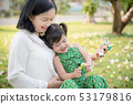 Grandmother and granddaughter sitting in park 53179816