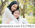 Grandmother and granddaughter sitting in park 53179822