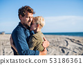 Young couple standing outdoors on beach, hugging. Copy space. 53186361