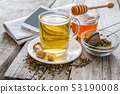 Herb tea in glass cup with honey 53190008