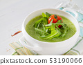 Arugula and tomatoes puree soup in white bowl 53190066