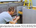 A carpenter is building a drawers garbage bin 53193029