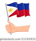 Hand holding and waving the national flag of Philippines. Fans, independence day, patriotic concept 53193933