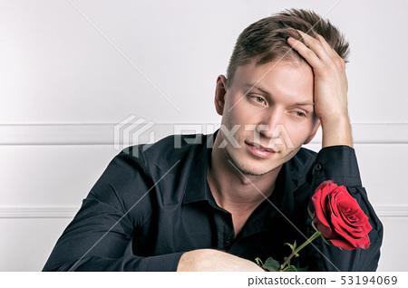 Handsome man wearing black shirt holding a rose 53194069
