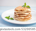 Pancakes stacked and topping with honey. 53200585