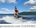 Young pretty slim brunette woman riding wakeboard 53205062