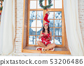 Beautiful young brunette woman wearing red pajamas sitting home by the window 53206486