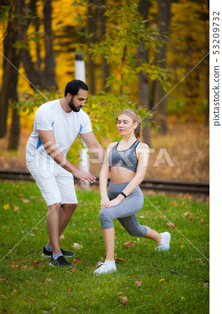 Fitness. Personal Trainer Takes Notes While Woman Exercising Outdoor 53209732