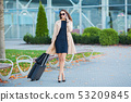 Young casual female goes at airport at window with suitcase waiting for plane 53209845