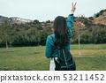backpacker standing outdoor raise one hand 53211452
