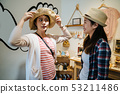 Girlfriends on shopping spree trying ladies hats 53211486