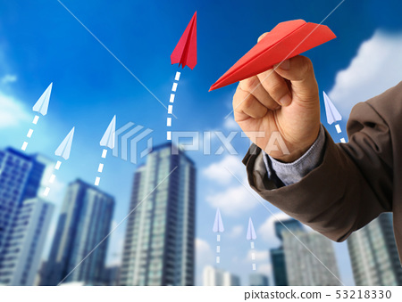 Business man in suit holding red paper airplane 53218330