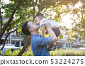 Father lifting son in hand and pretending to wheel 53224275