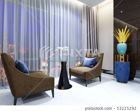 A table with two easy chairs in the lounge area of 53225292