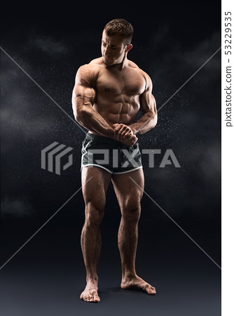 Young athlete showing his muscles at camera 53229535