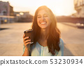 Happy woman walking through city street with takeaway coffee 53230934