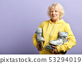 Active senior woman in yellow sports hoodie holding roller-skates posing indoors 53294019