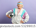 Positive elderly lady holds sparkling disco ball, dressed smiling at camera. 53299015