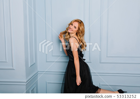 Pretty young lady wearing black elegant lace dress, enjoying photoshoot, posing in studio, room with 53313252