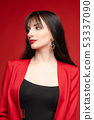 Young brunette model in red costume posing near 53337090