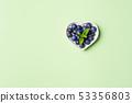 Heart of fresh blueberries on pastel green 53356803