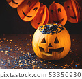 Halloween carved squash and confetti. Dark 53356930