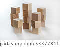 Stacks of wooden toy cubes creating small towers on white board 53377841