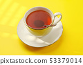 Sun shines over cup of hot tea with silver spoon on yellow board. 53379014