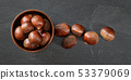 Tabletop photo - small wooden bowl with chestnuts, some spilled on stone like working board 53379069