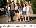friends with backpacks hugging walking in the city 53557014