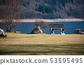 View of the Molveno lake with benchon the lawn 53595495