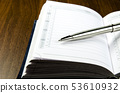 Closeup view of a metal pen lying on the diary 53610932