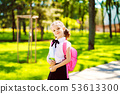 Smiling student girl wearing school backpack and holding exercise book. Portrait of happy Caucasian 53613300