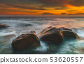The rock and smooth sea wave in the sunset time. 53620557