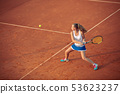 Woman playing tennis on clay court, with sporty outfit and healthy lifestyle 53623237