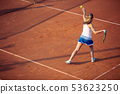 Young woman playing tennis on clay. Forehand. 53623250