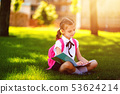 Little school girl with pink backpack sitting on grass after lessons and read book or study lessons 53624214