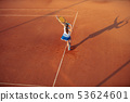 Woman playing tennis on clay court, with sporty outfit and healthy lifestyle 53624601