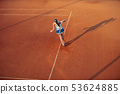 Woman playing tennis on clay court, with sporty outfit and healthy lifestyle 53624885