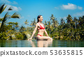 Woman in tropical vacation sitting in the water of pool 53635815