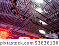 A dramatic view of the red corner of a regular boxing ring. Ropes in the corner of the ring. 53636136