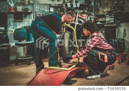 Mechanic and his helper repairing a motorcycle in a workshop 53639156