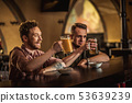 Cheerful friends drinking draft beer in a pub 53639239