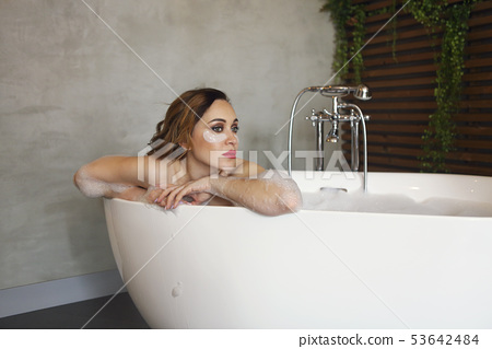 Happy young woman relaxing in bathtub 53642484