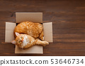 Cute ginger cat in carton box on wooden table 53646734