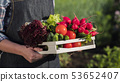 Side view of farmer holds a wooden box with a set of fresh ripe vegetables from his garden. Close-up 53652407